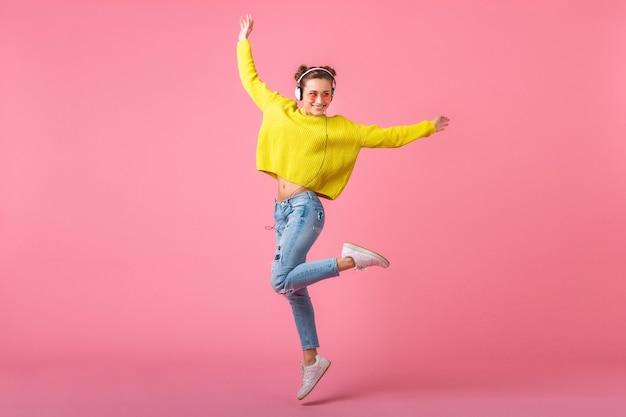 Привлекательная счастливая смешная женщина прыгает, слушая музыку в наушниках, одетая в красочный стиль хипстера, изолированного на розовой стене, в желтом свитере и солнцезащитных очках, веселится Бесплатные Фотографии