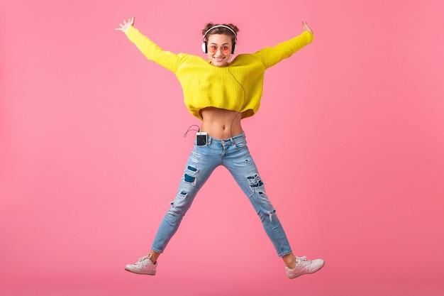 ピンクの壁に分離されたヒップスターのカラフルなスタイルの服を着て、黄色のセーターとサングラスを身に着けて、楽しんでヘッドフォンで音楽を聴いてジャンプする魅力的な幸せな面白い女性 無料写真