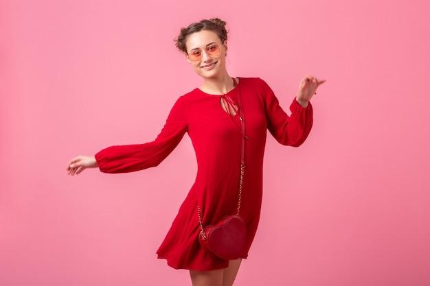분홍색 벽 절연, 봄 여름 패션 트렌드, 세인트 발레 나이트의 날, 낭만적 인 분위기의 유혹 소녀에서 실행 점프 빨간색 유행 드레스에 매력적인 행복 미소 세련된 여자 무료 사진