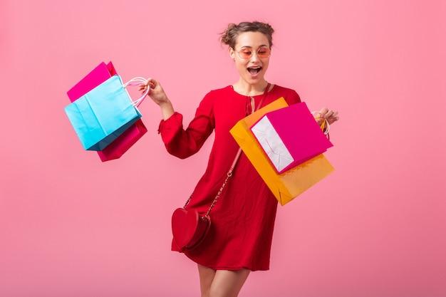 고립 된 분홍색 벽에 화려한 쇼핑 가방을 들고 빨간색 유행 드레스에 매력적인 행복 미소 세련 된 여자 쇼핑 중독, 판매 흥분, 패션 트렌드 무료 사진