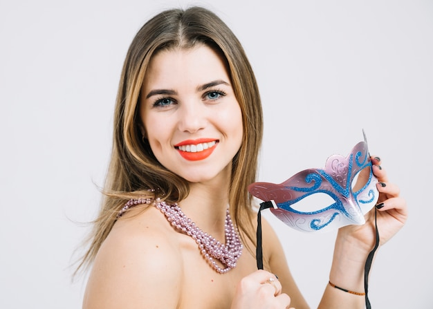 Attractive happy woman holding carnival mask on white backdrop Free Photo