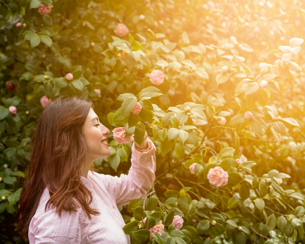 Attractive happy woman holding pink flower growing on green twig Free Photo