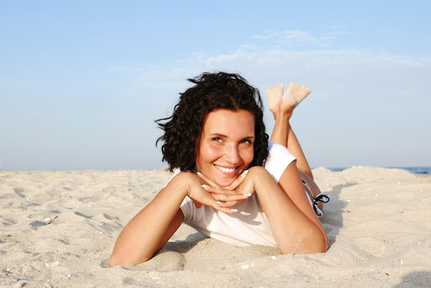 ビーチに横になってカメラを見ている魅力的な幸せな女性 無料写真