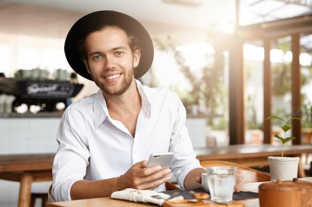 レストランでのコーヒーブレーク中に彼の電子デバイスで無料のwifiを使用して、ソーシャルネットワークとインターネットの閲覧を介してトレンディな帽子のテキストメッセージで魅力的な幸せな若いひげを生やした男 無料写真