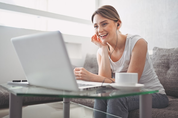 Attractive happy young student studying online at home, using laptop computer, headphones, having video chat, waving. remote work, distance education. video conference or virtual event on quarantine Premium Photo