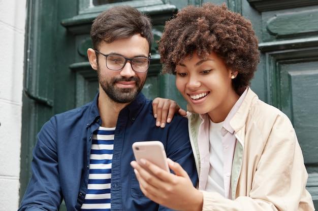 Attraente hipster e la sua ragazza dalla pelle scura guardano video divertenti online Foto Gratuite