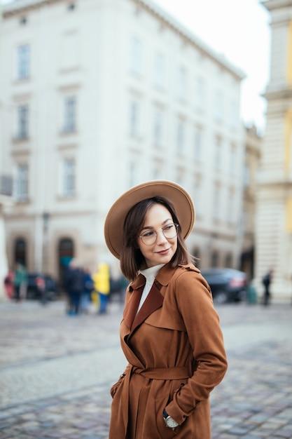 Привлекательный в современном коричневом пальто позирует на улице в центре города Бесплатные Фотографии