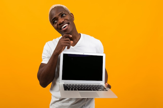 Attractive joyful smiling american man holding laptop with mockup and dreaming on yellow background Premium Photo