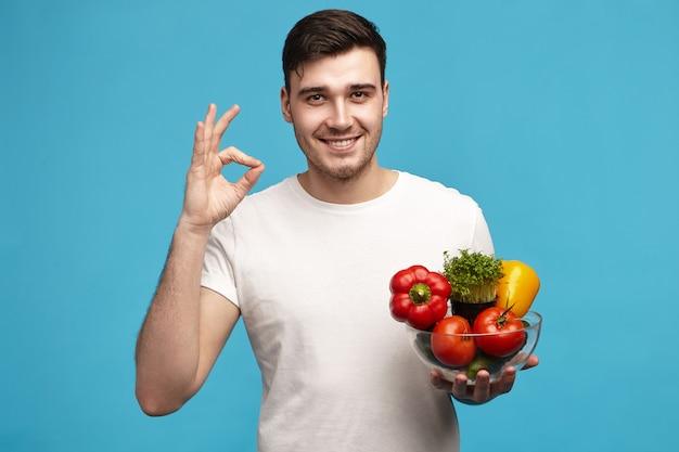 Привлекательный радостный молодой клиент или шеф-повар со счастливой улыбкой позирует в студии Бесплатные Фотографии