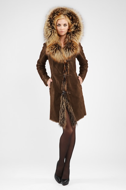 Attractive lady in brown sheepskin coat posing with fur hood on her head Premium Photo