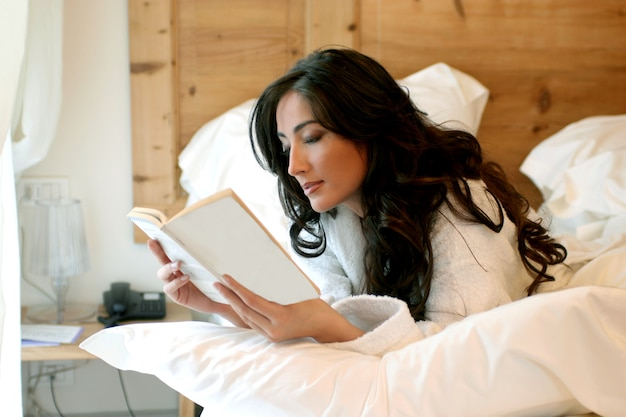 Attractive lady reading book layed down on bed Premium Photo