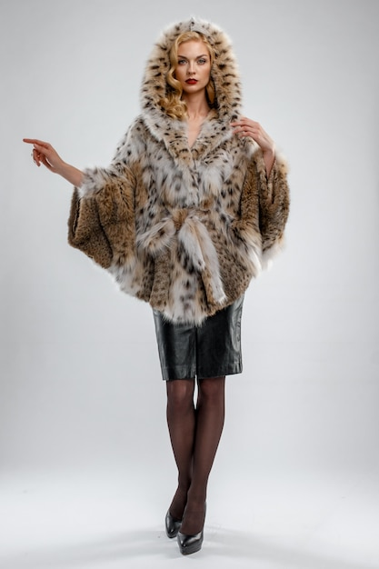 Attractive lady in spotted fur coat. perfect makeup, red mat lips and blue eyes. Premium Photo