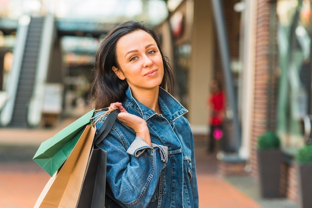 Attractive lady with shopping bags in mall Free Photo