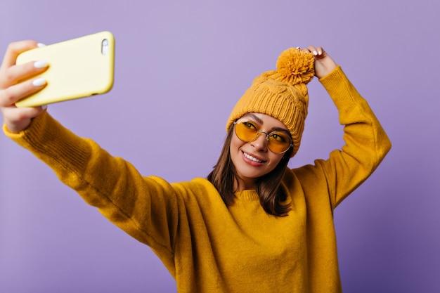 ソフトな機能を備えた魅力的な女性は、黄色いスマートフォンで自分撮りをします。機嫌の良いスラブ学生の肖像画 無料写真
