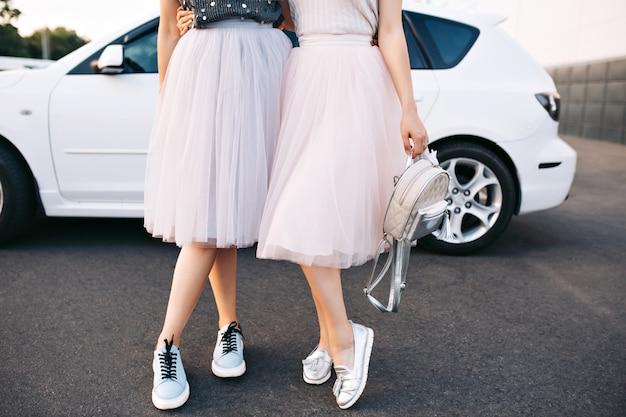 Gambe attraenti di modelle in gonne di tulle e scarpe da ginnastica su auto bianca. Foto Gratuite