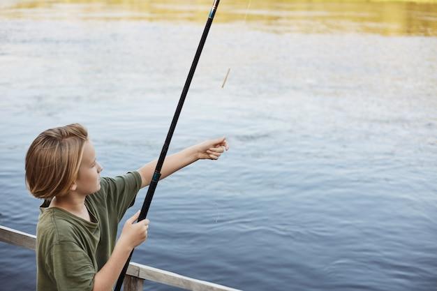 釣り竿を川に投げる魅力的な小さな男は、大きな魚を捕まえたいと思っています。川や湖の近くで自然に週末を過ごし、非常に集中しています。 無料写真