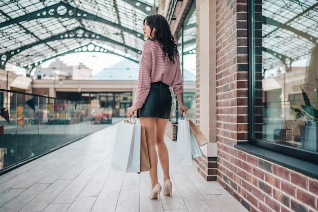 아늑한 니트 스웨터, 가죽 짧은 치마와 하이힐에 매력적인 긴 다리가있는 갈색 머리 여자, 손에 종이 가방 무리와 함께 쇼핑몰을 걷고 프리미엄 사진