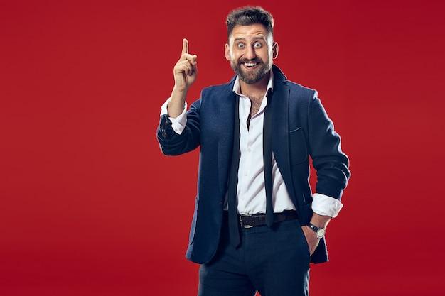 Привлекательный мужской поясной передний портрет на красной стене. молодой эмоционально удивленный бородатый мужчина что-то представляет. человеческие эмоции, концепция выражения лица. Бесплатные Фотографии
