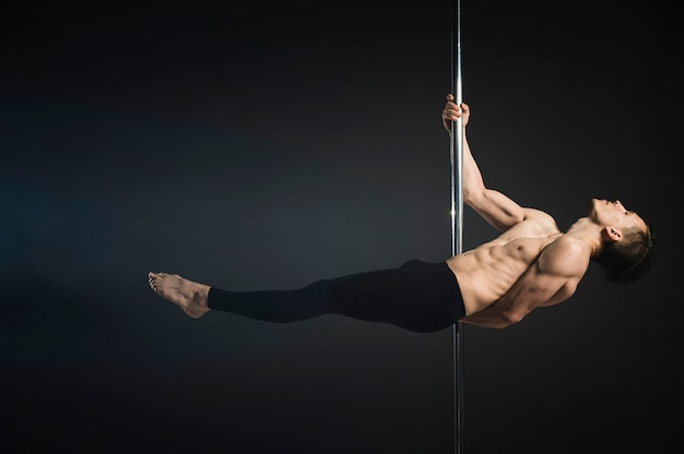 Attractive male model performing a pole dance Free Photo
