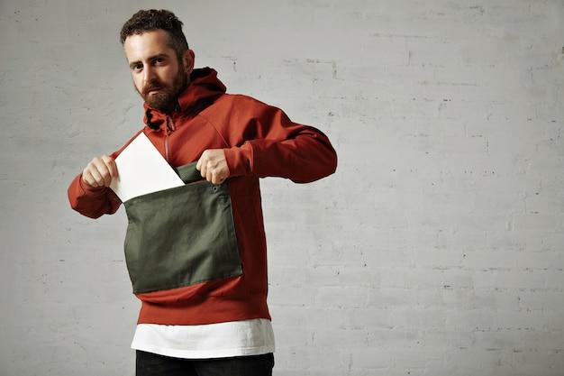 Привлекательная модель-мужчина вынимает чистый белый лист бумаги из переднего кармана его красно-серой куртки на белом Бесплатные Фотографии