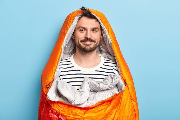 Привлекательная модель-мужчина с темной бородой и усами, позирует в удобном спальном мешке, на летних каникулах у реки, спит в палатке, ночует под небом, изолирована над синей стеной Бесплатные Фотографии
