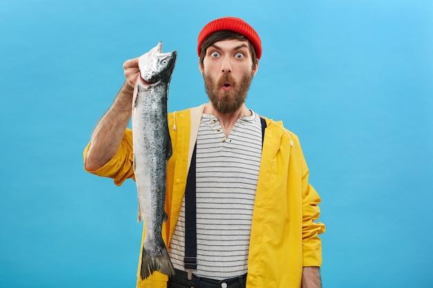 赤い帽子に身を包んだひげを持つ魅力的な男性、黄色いレインコート、虫眼鏡の目で見て巨大な魚を抱え、以前はそのような大きな魚を捕まえなかったショックで口を開けたオーバーオール 無料写真