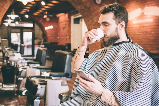Attractive man is sitting in chair in barbershop and drinking some tea. also he is looking at the phone and reading something from it. he is waiting for a hairdresser. Premium Photo