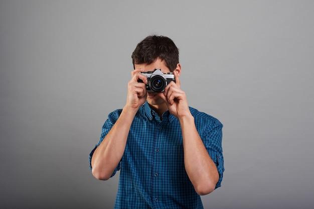 ヴィンテージカメラで写真を作る魅力的な男 無料写真