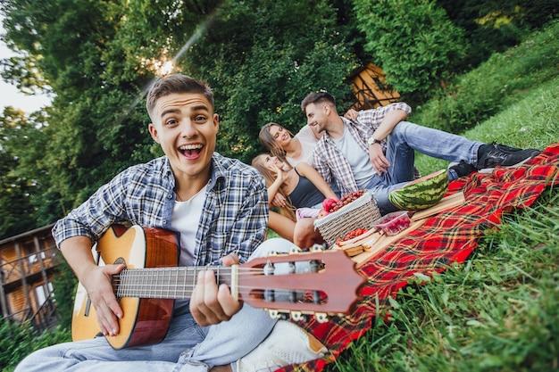 Привлекательный мужчина сидит в траве и играет на гитаре, он на пикнике с тремя друзьями Premium Фотографии