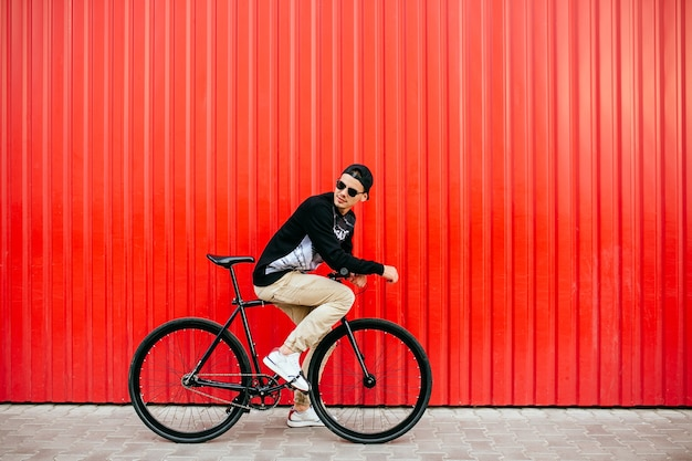 Attractive man in sunglasses, sitting on professional bike, riding, looking back Free Photo