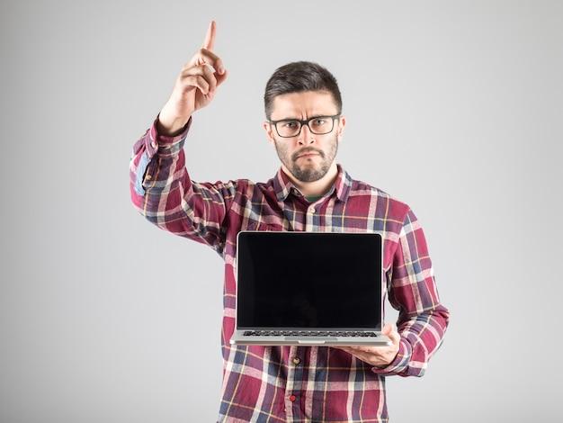 彼の人差し指を示す空白のラップトップを持つ魅力的な男 Premium写真