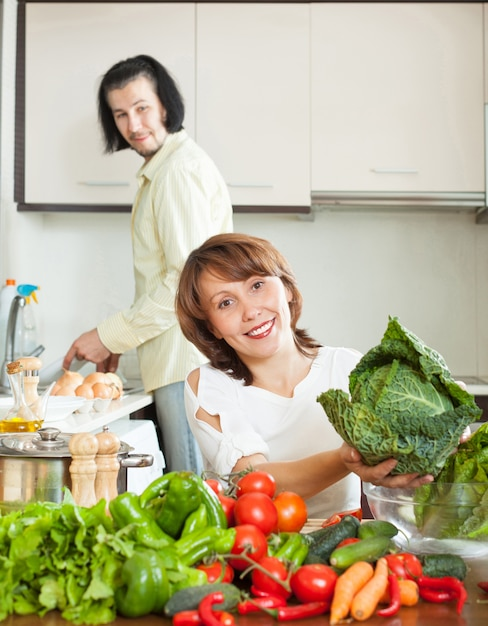 An attractive man and woman with vegetables in the kitchen Free Photo