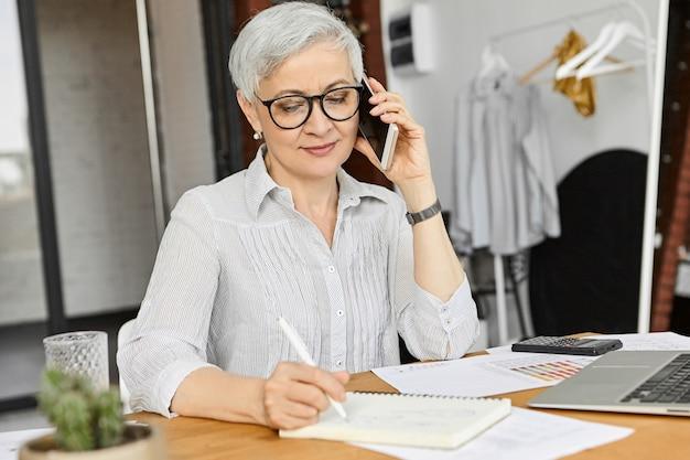 Amministratore delegato donna europea matura attraente in camicetta e occhiali con conversazione telefonica e prendere appunti contemporaneamente, annotare informazioni importanti. gadget elettronici moderni e comunicazione Foto Gratuite