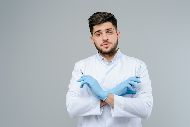 Attractive medical doctor in gloves with suringes isolated over grey background Premium Photo