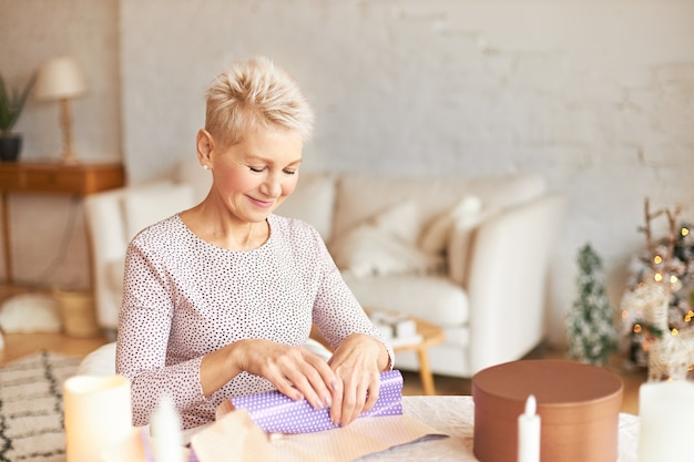 リビングルームのテーブルに座って、ギフトペーパーで夫へのクリスマスプレゼントを包む金髪の短いヘアカットを持つ魅力的な中年の女性 無料写真