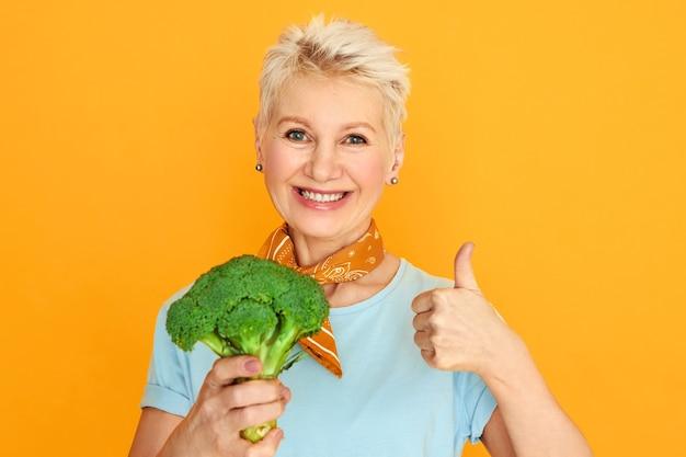 新鮮なブロッコリーを保持し、健康的な有機食品を選択してカメラに微笑んでいる短いピクシーの髪を持つ魅力的な中年の女性。 無料写真