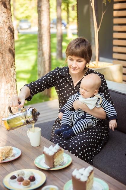 ヨーロッパの夏の屋外カフェで小さな赤ちゃんを持つ魅力的なママ Premium写真