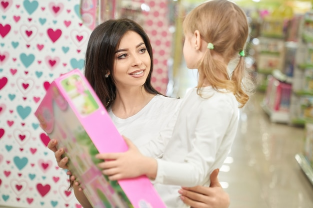 娘に新しいおもちゃを提示する魅力的な母親 無料写真