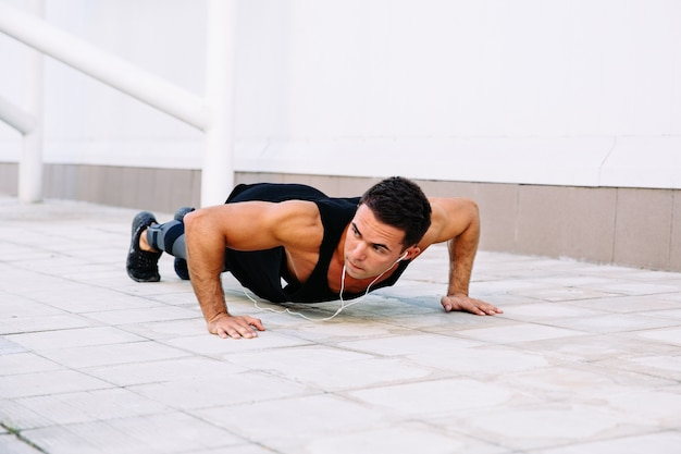 Attractive muscular guy doing push-ups exercises, during workout outdoors Free Photo