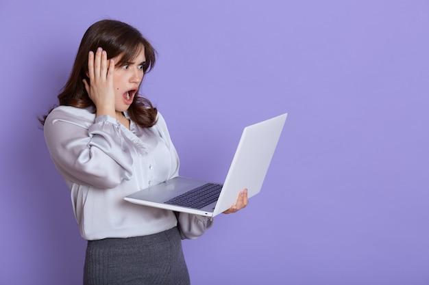 손에 노트북과 매력적인 긴장 젊은 비즈니스 여자, 충격 된 표정으로 장치의 화면을보고, 그녀의 머리를 손으로 만지고, 입을 넓게 열어두고, 라일락 벽에 서있다. 무료 사진