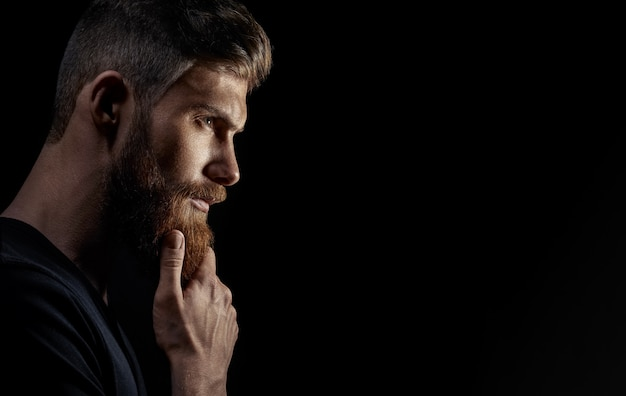 Attractive pensive young bearded man looks into the distance Premium Photo