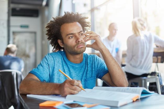 파란색 티셔츠에 매력적인 잠겨있는 젊은 남성 학생, 코 워킹 카페에서 집에서 일하는 동안, 작문 작성, 영어 또는 문학 준비, 사려 깊은 표정을 갖는 동안 공상 무료 사진