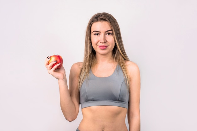 Attractive positive woman with apple Free Photo