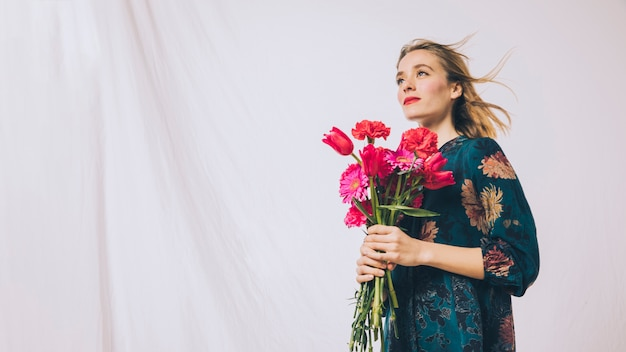 Attractive positive woman with bouquet of flowers Free Photo