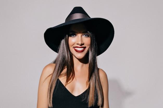Привлекательная симпатичная молодая женщина с дымными глазами и черными губами в шляпе и черном платье позирует перед стеной. хэллоуин, маскарад, вечеринка, праздник Бесплатные Фотографии