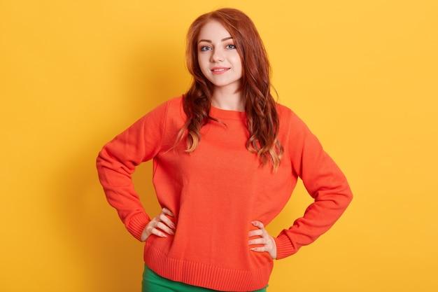 黄色の壁に立っているカジュアルなオレンジ色のプルオーバーを着て、魅力的な笑顔でカメラを直接見ている魅力的な赤い髪の女の子。前向きな感情を表現します。 無料写真
