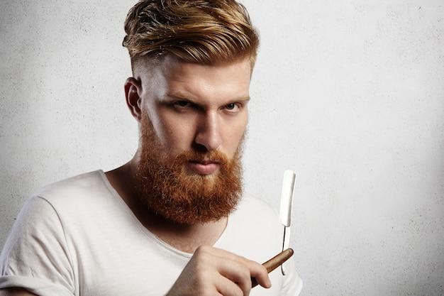 スタイリッシュなヘアカットと厚いひげを備えた魅力的な赤毛のヒップバーバーで、深刻な顔の表情を持つ喉を剃るカミソリを持っています。 無料写真
