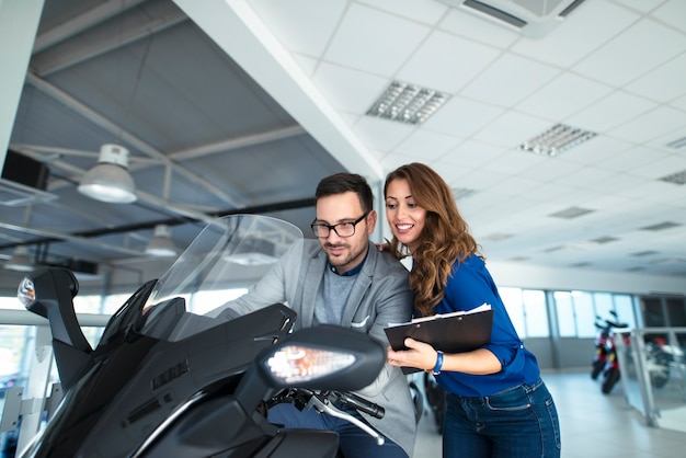 どのバイクを購入するかを顧客に支援する魅力的なセールスウーマン 無料写真