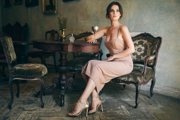 Attractive seductive sensual stylish woman in boho dress sitting vintage retro cafe drinking wine from glass wearing golden luxury high heeled shoes Free Photo