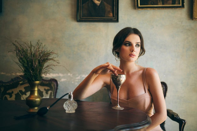 Attractive seductive sensual stylish woman in boho dress sitting vintage retro cafe drinking wine from glass Free Photo